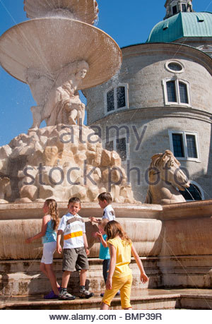 Children enjoy the cool water from the Residenzplatz fountain on a hot summer's day in Salzburg, Austria. - Stock Photo