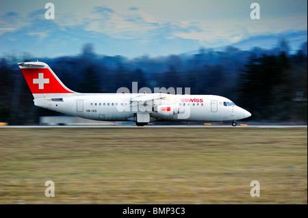 An Avro RJ100 taking off from Geneva airport on a winter's evening, motion blur on the background. - Stock Photo