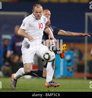 Wayne Rooney of England (10) attacks against the United States as Jay DeMerit (r) defends during a 2010 World Cup - Stock Photo