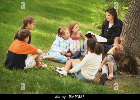 Edmonton, Alberta, Canada; A Woman Teaches A Group Of Children In A Park - Stock Photo
