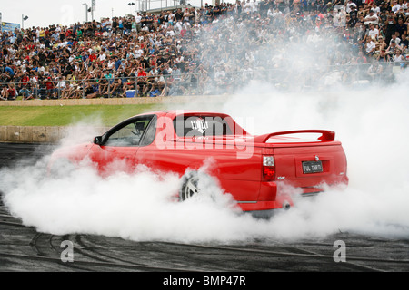 Australian Holden Commodore utility (ute, or pick up truck) performing a burnout at an Australian summer car show - Stock Photo