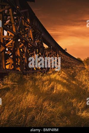 Alberta, Canada; A Train Trestle In A Sunset - Stock Photo