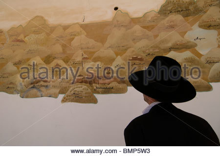 Ultra orthodox Jew observing a wall painting depicting old map of the holyland in an abandoned structure at the - Stock Photo