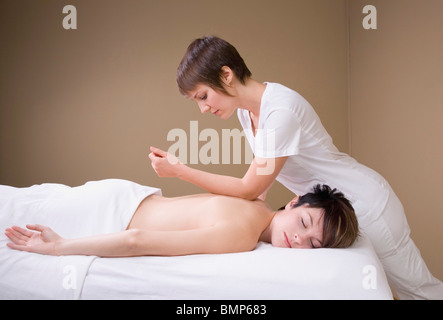 A Woman Getting A Massage From A Massage Therapist - Stock Photo