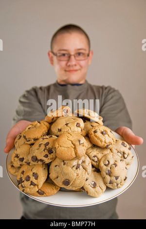 A Boy Holding A Plate Of Chocolate Chip Cookies - Stock Photo