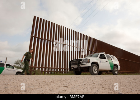 U.S. Border Patrol agent along the border wall between the United States and Mexico near Hidalgo, Texas, and Reynosa, - Stock Photo