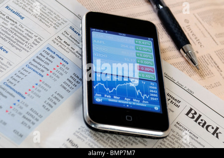 an iphone with a stockmarket application open lying on the financial pages of a newspaper - Stock Photo