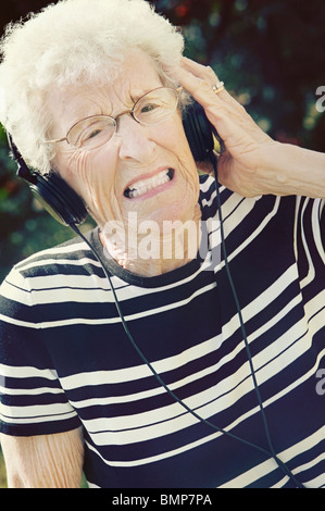 Sherwood Park, Alberta, Canada; A Senior Woman Cringing At The Music Coming Through Her Headphones - Stock Photo