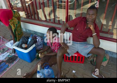 Ambulant salesmen on a sidewalk in Maputo, Mozambique. - Stock Photo