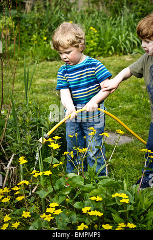 Two young brothers in a garden filling a pond with water using a yellow hose pipe. - Stock Photo