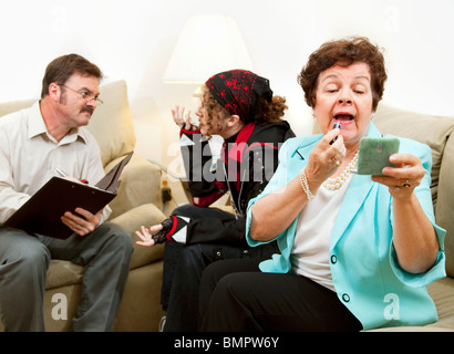 Vain disinterested mother puts on makeup while her troubled teen daughter talks to a counselor.  - Stock Photo