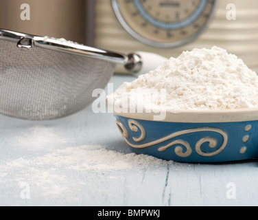 A Dish Full Of Flour With A Sieve and Scales In The Background - Stock Photo