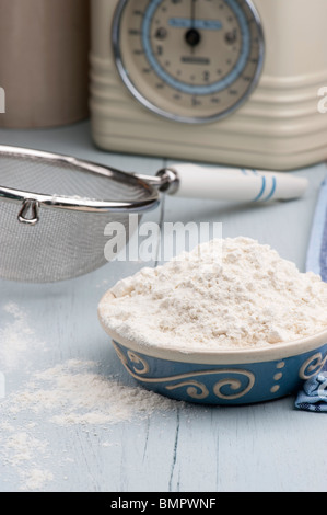 A Dish Full Of Flour With A Sieve and Scales In The Background, On A Wooden Kitchen Table - Stock Photo