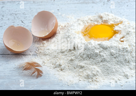 A Cracked Egg In Some Flour, With The Shell and A Hen Feather To The Side - Stock Photo