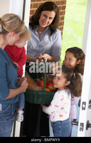 Knoxville, Tennessee,United States Of America; A Woman With Her Daughters Delivering Food In A Basket To A Woman - Stock Photo
