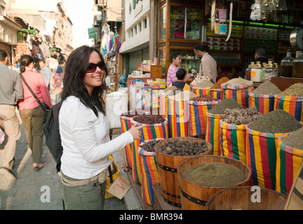 Western woman tourist buying spices in the Khan al Khalili market, the islamic quarter, Cairo Egypt - Stock Photo