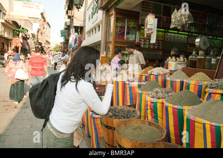A western woman tourist buying spices in the Khan al Khalili market, the islamic quarter, Cairo Egypt - Stock Photo