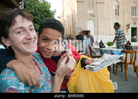 A young egyptian boy making friends with a western tourist to try and sell his wares, The Islamic quarter, Cairo - Stock Photo