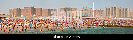 A holiday crowd of over a million sunbathes and swims on the beach of the famous Coney Island amusement park in - Stock Photo