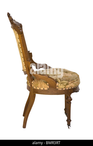 Eastlake Victorian antique wood carved upholstered chair from a side view. Associated with the Victorian era. Isolated - Stock Photo