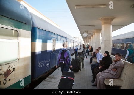 Western tourists arriving on an early moring train, Luxor railway station, Luxor, Egypt - Stock Photo