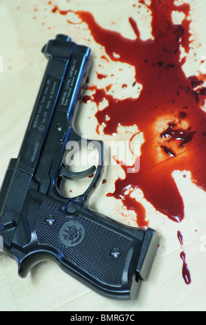 an automatic pistol with bloodstains (replica gun) - Stock Photo