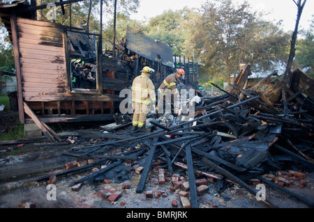 Firemen inspect rubble after house fire. - Stock Photo