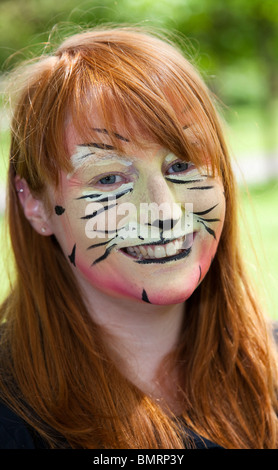 Young girl with her face painted to look like a tiger at the West End Festival held in Kelvingrove Park, Glasgow - Stock Photo