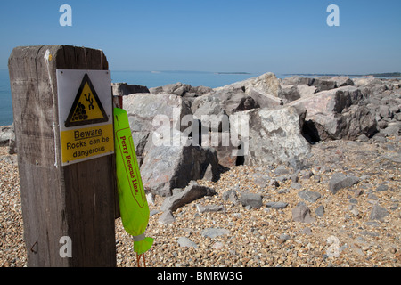 rescue line on post at seaside by dangerous rocks sign - Stock Photo