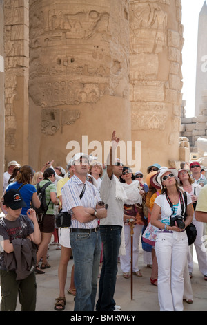 Tour guide Egypt; Tourists on a guided tour in the Hypostyle Hall,  the Temple of Karnak, Luxor, Egypt - Stock Photo