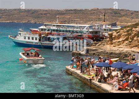 Sailing boat and tourists at the Blue Lagoon, Comino, Malta. - Stock Photo