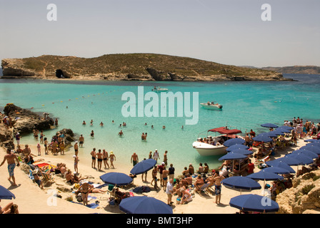 Tourists enjoying the clear waters of the Blue Lagoon, Comino, Malta. - Stock Photo