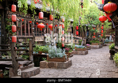 Early morning canal and street with restaurants and hanging chinese lanterns Lijiang Old Town Yunnan China - Stock Photo