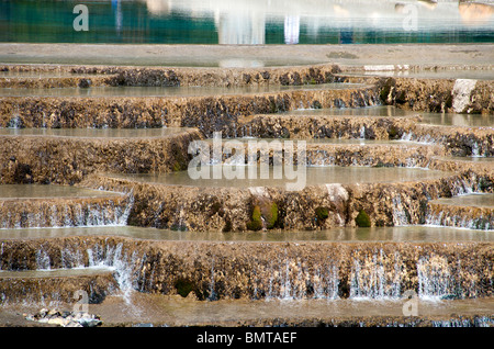 Water running over weir Yulong (Jade Dragon) Mountain near Lijiang Yunnan China - Stock Photo