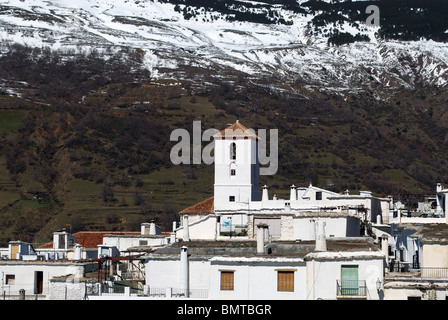 View over the town rooftops towards the church and snow capped mountains, Capileira, Las Alpujarras, Granada Province, - Stock Photo