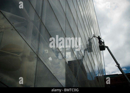 Window washers clean the massive glass curtain wall at the Rose Center of the American Museum of Natural History - Stock Photo