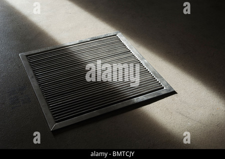 Steel grate in a concrete floor partially lit - Stock Photo