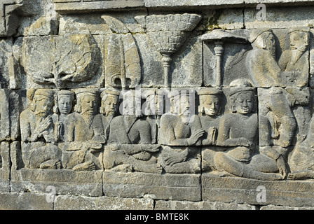 Indonesia-Java-Borobudur, Seated sages in cross-legged with folded hands. - Stock Photo