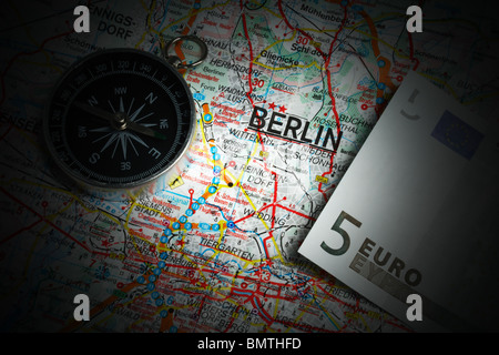 Compass and five euros on a map of Berlin - Stock Photo