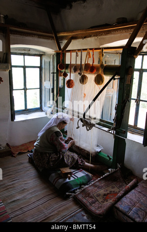 Cottage industry an elderly Turkish woman using a loom to make a wool carpet in the village of Etrim in the Aegean - Stock Photo