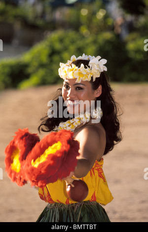 A Hawaiian hula dancer performs with feather gourd rattles ('uli'uli) on   Waikiki Beach during a luau for tourists - Stock Photo