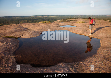 Hiker at vernal pool on top of granite dome Enchanted Rock State Natural Area Texas USA - Stock Photo