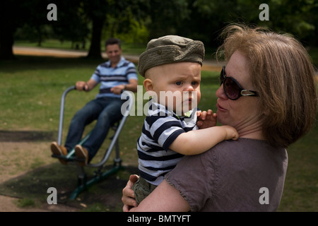 An eleven month-old toddler is held tightly by his 40-something aunt as daddy exercises behind. - Stock Photo
