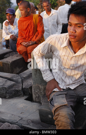 A young Cambodian man enjoys the sunset view off Phnom Wat Bakeng at Angkor, Cambodia - Stock Photo