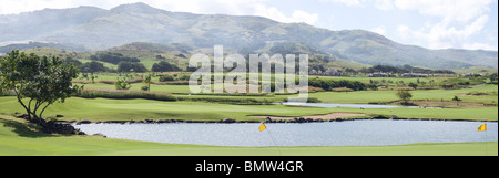 panoramic view of golf course with private luxury villas against cloudy sky background - Stock Photo