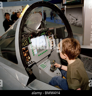 A young boy sits in BAE Systems Typhoon model cockpit. - Stock Photo
