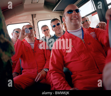 Pilots of the 'Red Arrows', Britain's Royal Air Force aerobatic team ride in crew bus after air show display. - Stock Photo