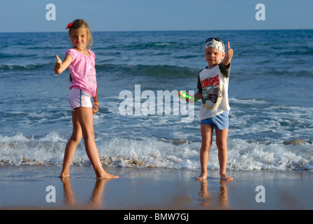 Little boy and girl thumbs up near sea - Stock Photo