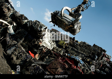 Scrap yard crane with crushed car with other crushed scrapped cars in pile. - Stock Photo