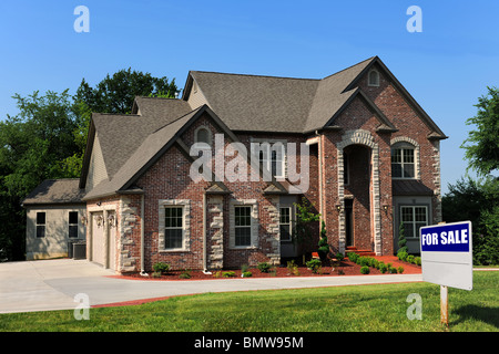 New house for sale with sign on front yard - Stock Photo
